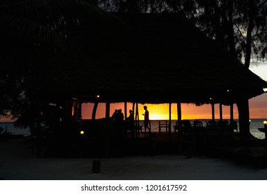 Silhouette of a Beach Bar against a Romantic Sunset with People in Zanzibar