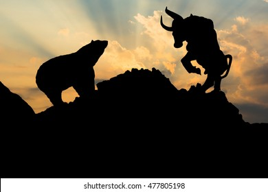 The silhouette of a bear and bull.