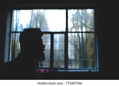 silhouette of a bearded man on a window background