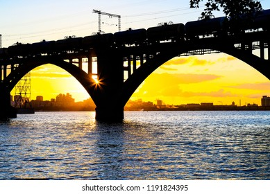 Silhouette of a beautiful arched railway bridge and train with cisterns on the Dnieper river at sunset. Dnipropetrovsk (Dnepr, Dnipro city , Dnepropetrovsk) Ukraine.