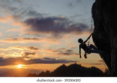 Silhouette of beautiful athletic woman climbing steep rock wall against amazing sunset scene in the mountains. Girl is hanging on one hand and looking up.