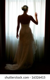 Silhouette of a beautiful bride in a traditional white wedding dress, stood by window.