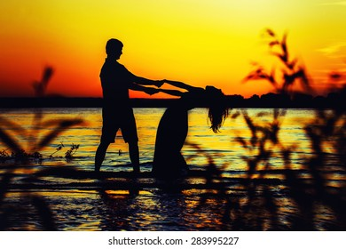 A silhouette of beautiful dancing couple at a seashore at golden summer sunset background.