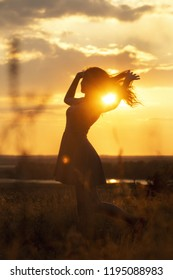 silhouette of a beautiful dreamy girl in a dress at sunset in a field, a young woman with her hair is enjoying nature, concept of relaxion on nature and emotions