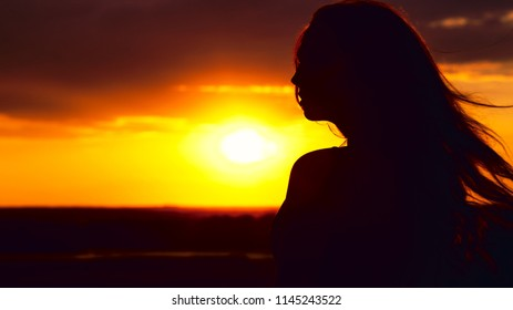 silhouette of a beautiful dreamy girl at sunset in a field, face profile of young woman enjoying nature