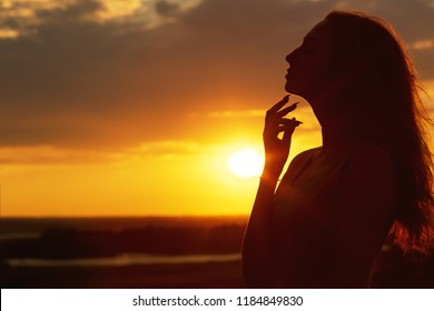 silhouette of a beautiful dreamy girl at sunset in a field, face profile of young woman on nature