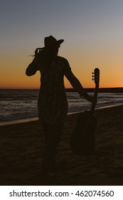 Silhouette of beautiful elegant female with guitar at the beach, sunset outdoors background. Back view