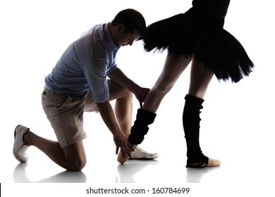 Silhouette of a beautiful female ballet dancer and her instructor isolated on a white background. Ballerina is wearing a black leotard, black tutu and pointe shoes.