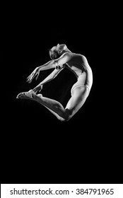 Silhouette of beautiful female in dancing jumping or flying on dark background. Black and white photography