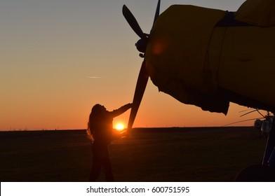 silhouette of a beautiful female pilot executing preflight maneuvers in sunset light