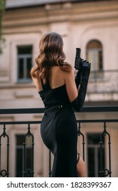 silhouette of beautiful girl in elegant black dress. Young woman holding gun in her hands. fashion model in carnival image of  dangerous sexy spy.  retro lady, vintage wave blond hairstyle. Back view