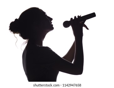 silhouette of beautiful girl with hand-picked hair singing into microphone, profile of young woman face performing lyric song on white isolated background concept music and hobby