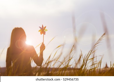 Silhouette of Beautiful girl holding wind toy or wind turbine or pinwheel and wool hat at meadow on winter season in morning.
