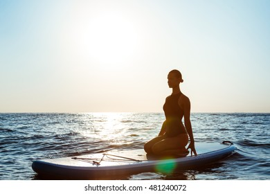 Silhouette of beautiful girl practicing yoga on surfboard at sunrise.