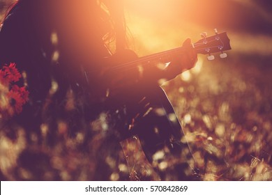 Silhouette Beautiful girl relax by playing acoustic guitalele on the flower grass fieid with flower basket at sunset. vintage color effect