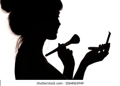 silhouette of beautiful happy girl doing make-up, profile of female face on white isolated background with mirror, powder and brush, concept of fashion and beauty