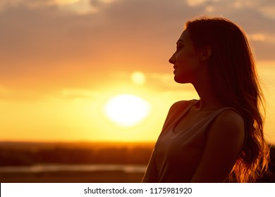 silhouette of a beautiful romantic girl at sunset in a field, face profile of young woman enjoying nature