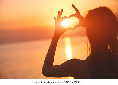silhouette of a beautiful sexual girl against the sea and sunset. happy woman enjoying summer vacation. Woman shows a heart by hands