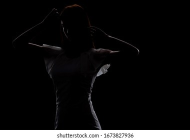 Silhouette of a beautiful slender girl in a white dress on a black background