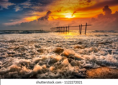 Silhouette of beautiful sunset with old wooden bridge and strong wave in the sea at Khao Pilai Beach in Phang Nga, Thailand. Beautiful sunset and sea in Background