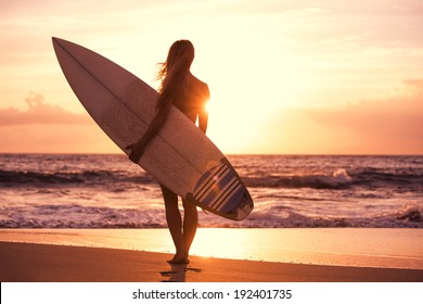 Silhouette of beautiful surfer girl on the beach at sunset