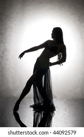 Silhouette of the beautiful woman dancing on glass.