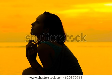 SILHOUETTE BEAUTIFUL WOMAN WITH GOLDEN SKYLIGHT REFLECTING ON OCEAN BACKGROUND