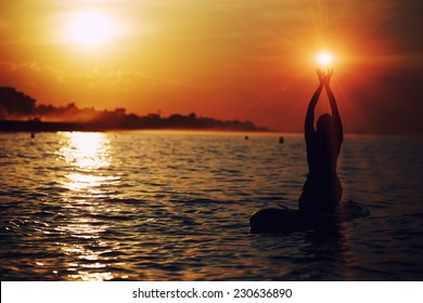Silhouette of beautiful woman holding sun in the hands during sup yoga meditation,yoga training in harmony with nature, silhouette of paddle board yoga performed by beautiful woman, spiritual concept