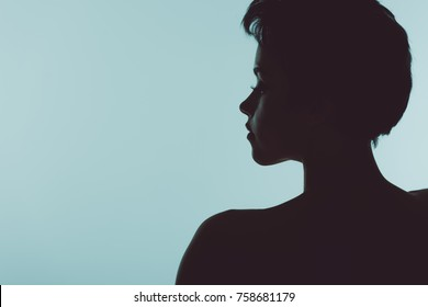 silhouette of beautiful woman looking away isolated on blue