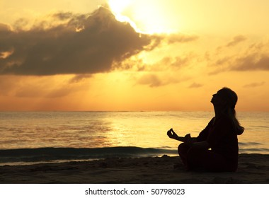 Silhouette of a beautiful woman meditating on the beach by the sea