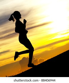 Silhouette of a beautiful woman running up the hill against yellow sky with clouds at sunset