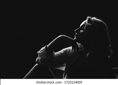 Silhouette of a beautiful young blonde girl in low key. Black and white art photo. Soft selective focus.