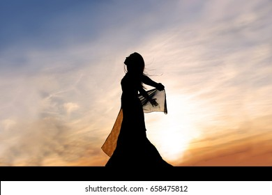 A silhouette of a beautiful, young, woman dancer, outside at sunset, praising God.