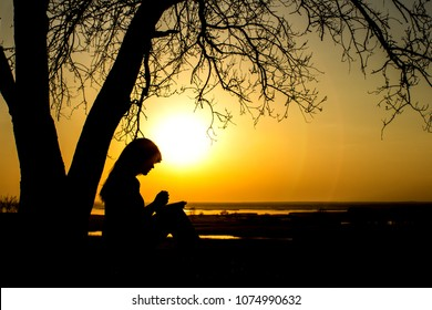 silhouette of beautiful young woman praying to God in the nature, femaleholds her hands on the Bible near the tree at sunset, the concept of religion and spirituality
