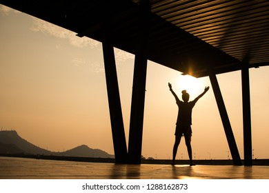The silhouette of a beautiful young woman standing in the arms at evening, at sunset, showing the power and freedom.