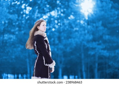 Silhouette beautiful young woman standing profile and looks wearing a brown coat in winter cold snowy scandinavian forest