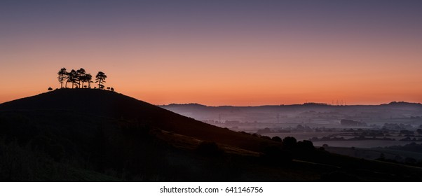 Silhouette before sunrise of a tree topped hill in England
