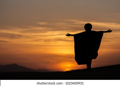 Silhouette of a berber man embracing the colorful sunset in desert Saharam Morocco