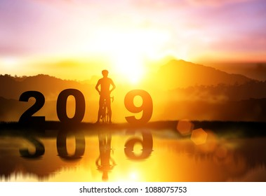 Silhouette bicycle in 2019 text on Water reflection sunset,Friendship in bicycle sport.happy new year