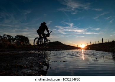 Silhouette of a bicycle and cyclist in the sunset close a watering hole.