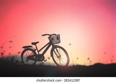 Silhouette bicycle in the meadow over beautiful sunset background.