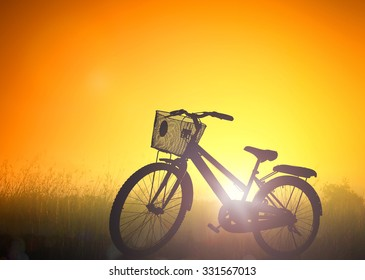 Silhouette bicycle in the meadow over beautiful golden autumn sunset background.