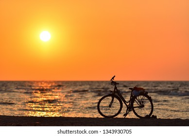 A silhouette of a bicycle standing on the beach of the Baltic Sea in Jurmala, Latvia. Evening. Orange sunset.