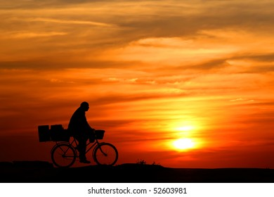 Silhouette of bicyclist on orange sunset's background