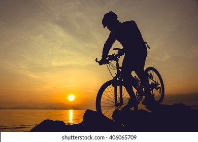 Silhouette of bicyclist riding the bike on a rocky trail at seaside, on colorful sunset sky background. Active outdoors lifestyle for healthy concept.