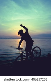 Silhouette of bicyclist riding the bike on rocky trail at seaside, on colorful sunset sky background. Active outdoors lifestyle for healthy concept. Action of winner or successful people.