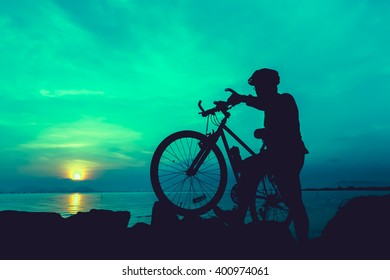 Silhouette of bicyclist standing with bike on a rocky trail at seaside, on colorful sunset sky background. Active outdoors lifestyle for healthy concept. Vintage style.