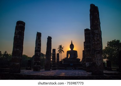 Silhouette of big buddha statue inside ruin temple at Sukhothai Historical Park, UNESCO World Heritage Site in Thailand.