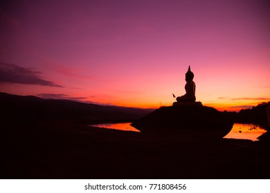silhouette of big buddha statue and reflection in sunset Thailand