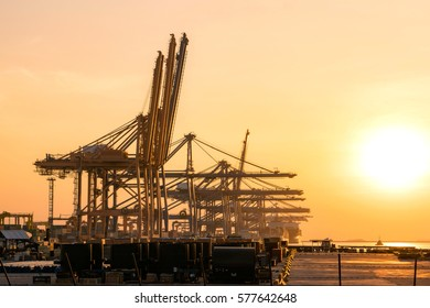 Silhouette Big Crane loading Industrial Container Cargo freight ship for import export logistics,Sunset time.
